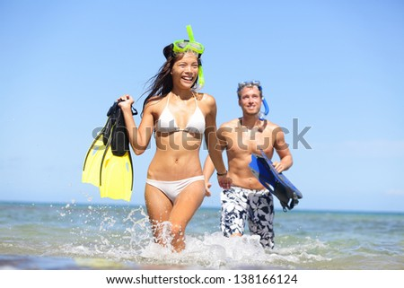 Happy couple beach summer vacation travel fun. Woman and man laughing with joy with snorkeling fins equipment on tropical beach under sunny blue sky. Multiracial couple, Asian woman, Caucasian man.