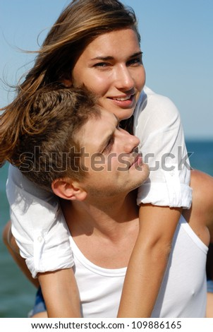 Happy couple beautiful young woman & handsome young man embracing outdoors on the bright sunny day over sea and blue sky background
