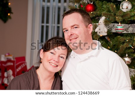 Happy couple beside a Christmas tree