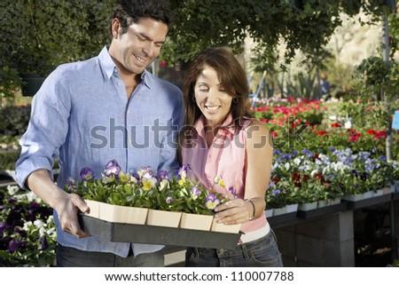 Happy couple buying flower plants at botanical garden