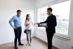 Happy Couple Buying New Home With Realtor Wearing Face Masks