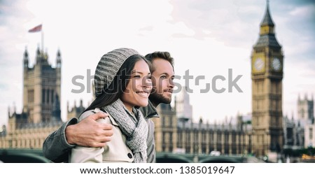 Happy couple by Big Ben Parliament, River Thames, London. Romantic young couple enjoying view during travel. Asian woman, Caucasian man in London, England, United Kingdom.