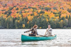 Happy couple canoeing in a lake in Canada - Colourful trees and leaves in background at autumn foliage peak - Young couple enjoying nature and adventure,  wanderlust and nature concepts
