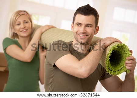 Happy couple carrying carpet together at moving house.