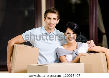 Happy couple carrying pasteboard boxes while moving to new house