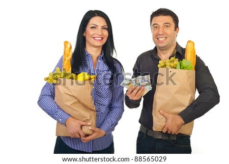 Happy couple carrying shopping paper bags with food and showing money banknotes  isolated on white background