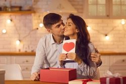 Happy couple celebrating Valentine's Day at home and enjoying spending time together and giving each other presents. Man kisses a woman holding a Valentine's card while sitting in a cozy kitchen.