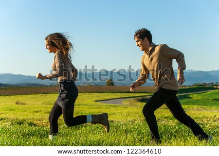 Happy couple chasing each other in countryside.