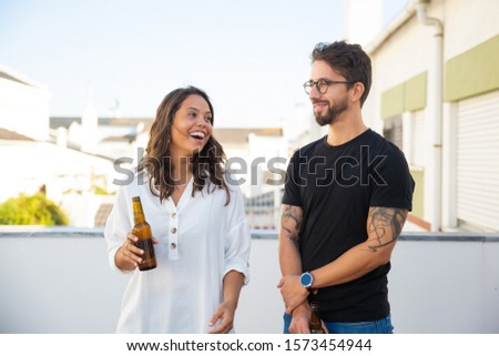 Happy couple chatting, laughing and drinking beer on outdoor terrace. Young man and women in casual meeting outside. Dating outside concept