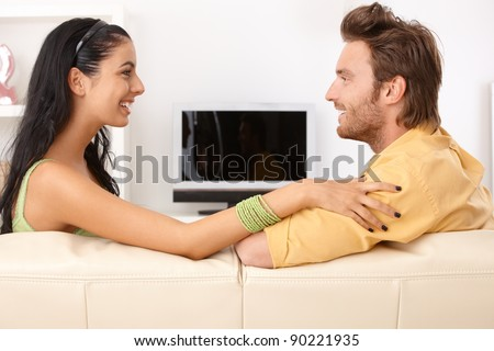 Happy couple chatting on sofa, side view.?