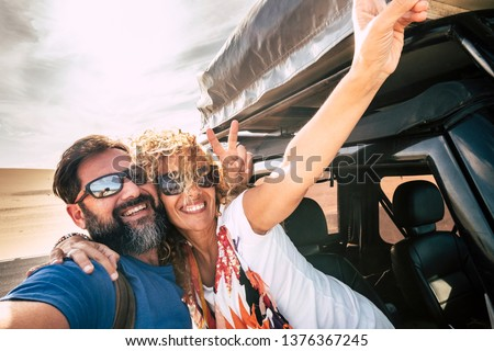 Happy couple cheerful and smile in selfie picture style together hugging with relationship and happiness during car travel - desert and sky in backgorund - joyful people in summer holiday