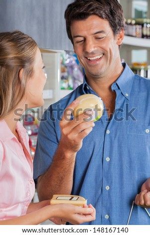 Happy couple choosing cheese at grocery store