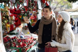Happy  couple  choosing Christmas souvenirs at Barcelona