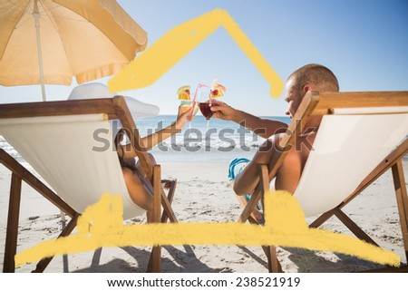 Happy couple clinking their glasses while relaxing on their deck chairs against house outline