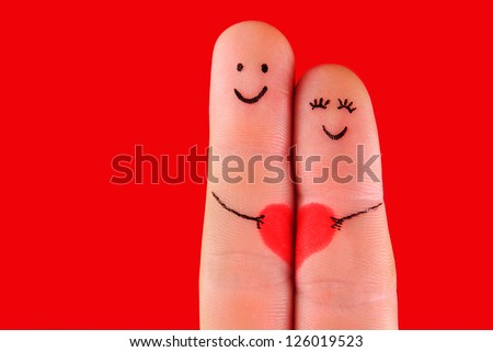 happy couple concept - a man and a woman hug,painted at fingers isolated on red background