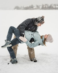 Happy couple dancing together in snow in winer day