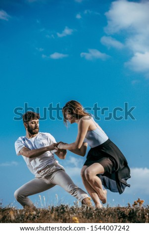 Happy couple dancing together outdoors. Caucasian man and caucasian woman enjoying a quality time together #1544007242