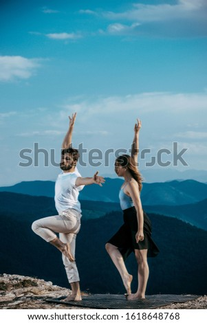 Happy couple dancing together outdoors. Caucasian man and Caucasian woman enjoying a quality time together practicing yoga on the top of the mountain