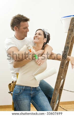 Happy couple doing home improvement. Holding painting tools, hugging and smiling to each other.