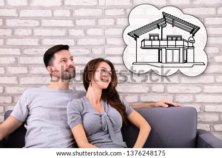 Happy Couple Dreaming Of Having Future Home While Sitting On Sofa #1376248175