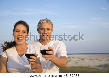 Happy couple drink wine on the beach and raise their glasses to the camera. Horizontal shot. - stock photo