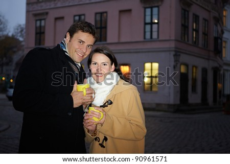 Happy couple drinking cups of tea in winter