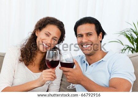 Happy couple drinking red wine sitting on the sofa at home
