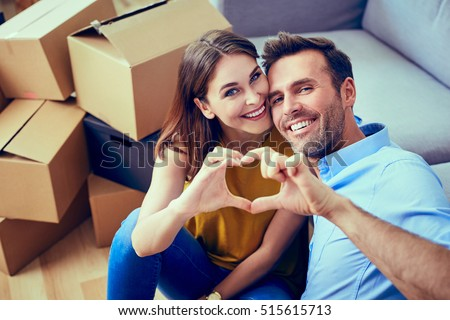 Happy couple during moving house showing heart sign #515615713