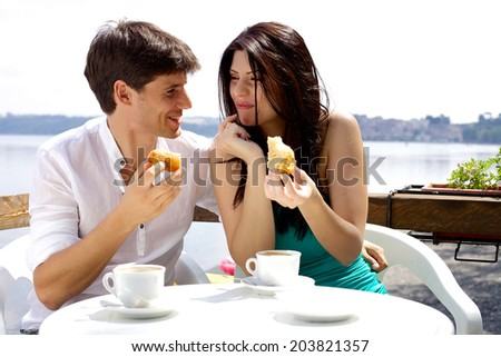 Happy couple eating cake in hotel in front of lake in Italy