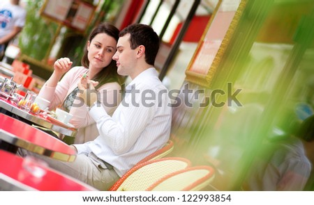 Happy couple eating delicious macaroons in a Parisian outdoor cafe