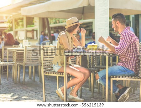 Happy couple eating fajitas sandwich and toasting beer in bar kiosk restaurant. Young people having fast meal sitting outdoor - Relationship concept - Focus on girl face - Warm cinematic filter