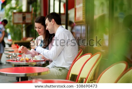 Happy couple eating macaroons in a Parisian outdoor cafe
