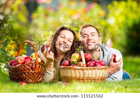Happy Couple Eating Organic Apples in Autumn Garden.Healthy Food.Outdoors.Park. Basket of Apples.Harvest concept .Smiling People Relaxing on Grass - stock photo