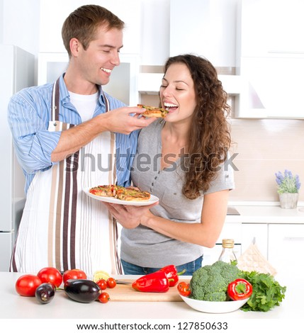 Happy Couple Eating Pizza Cooking Together Homemade Pizza Smiling Family in the kitchen Preparing And Tasting Food