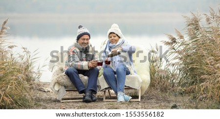 happy couple enjoy a winter day on the beach with drinking hot tea stock photo