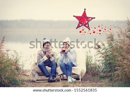 happy couple enjoy a winter day on the beach with drinking hot tea, christmas season stock photo