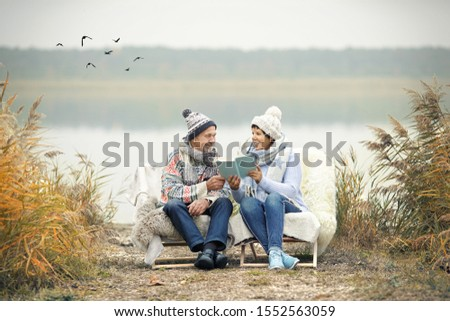 happy couple enjoy a winter day on the beach with reading a book, winter season stock photo