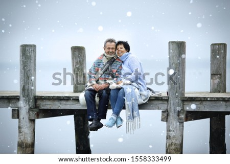 happy couple enjoy a winter day on the pier on warm blanket stock photo