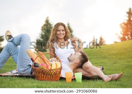Happy couple enjoying picnic. People having rest with much food, drinks. Girl smiling to camera.
