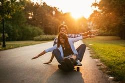 Happy couple enjoying ride on a long board.