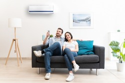Happy couple freshen up using air conditioner at home