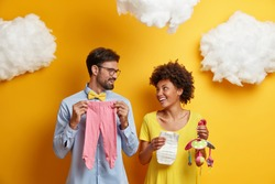 Happy couple future parents prepare for parenthood and giving birth to baby pose with infant items looks cheerfully at each other pose together against yellow wall. Healthy pregnancy family life