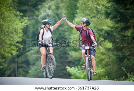 happy couple goes on a mountain asphalt road in the woods on bikes with helmets giving each other a high five