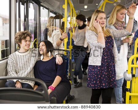 Happy couple going by bus with large group of people