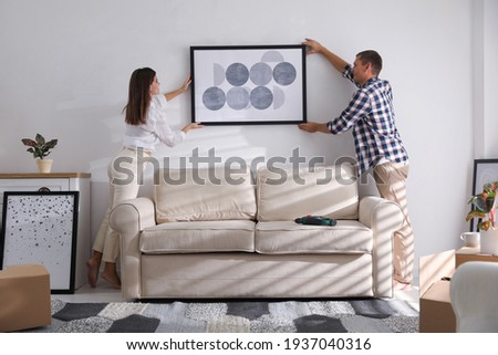 Happy couple hanging picture on white wall together. Interior design Foto d'archivio ©