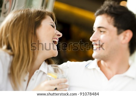 Happy couple having a drink and looking at camera