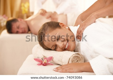 Happy couple having back massage in day spa.