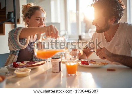 Happy couple having breakfast together in the kitchen Foto stock ©
