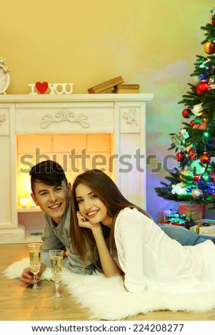 Happy couple having drinks by  fireplace in cozy dark living room on Christmas eve
