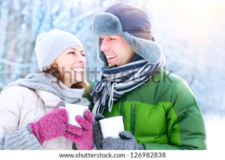 Happy Couple Having Fun Outdoors. Snow. Winter Vacation. Hot Drink Outdoor.